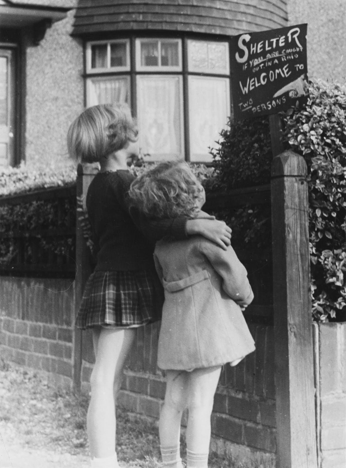 A black-and-white photograph of two small children looking up at a makeshift sign. The sign reads 'Shelter if you are caught out in a raid Welcome to two persons""