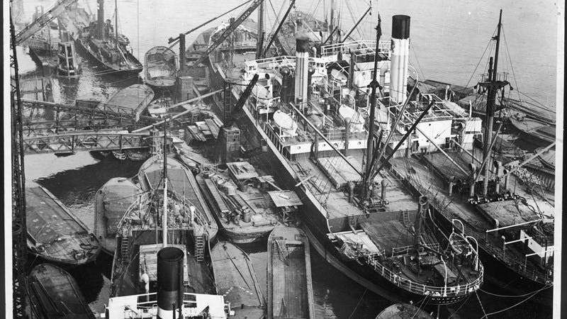 A black-and-white photograph showing busy scenes at the London Docks, with many barges and steamers close together and cranes dotted around the landscape.
