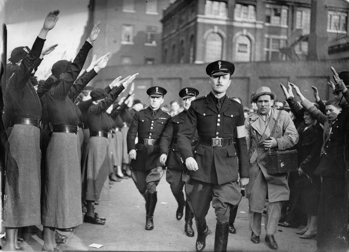 Black and white photograph of Oswald Mosley walking through a rally, while dozens of people around him make the Nazi salute.