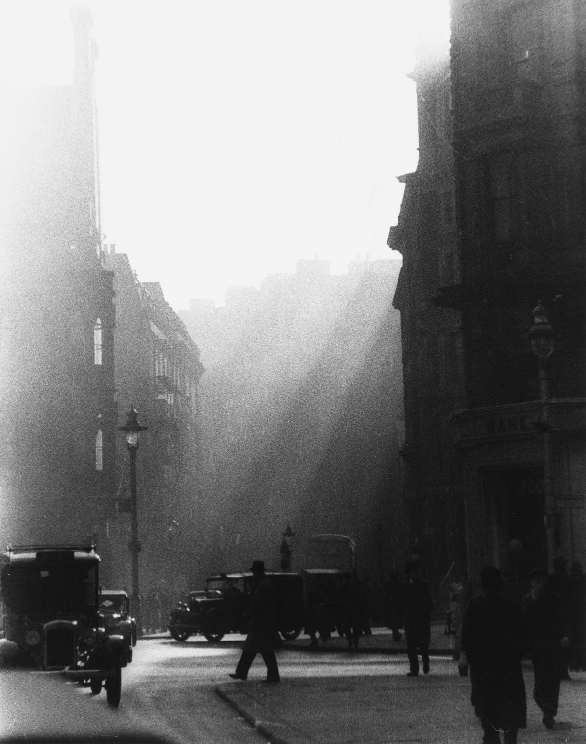 A black-and-white photograph of a London street. The image is dramatic and high-contrast. Sunlight streams down from above, and the streetlamps, cars, and people on the street are silhouettes.