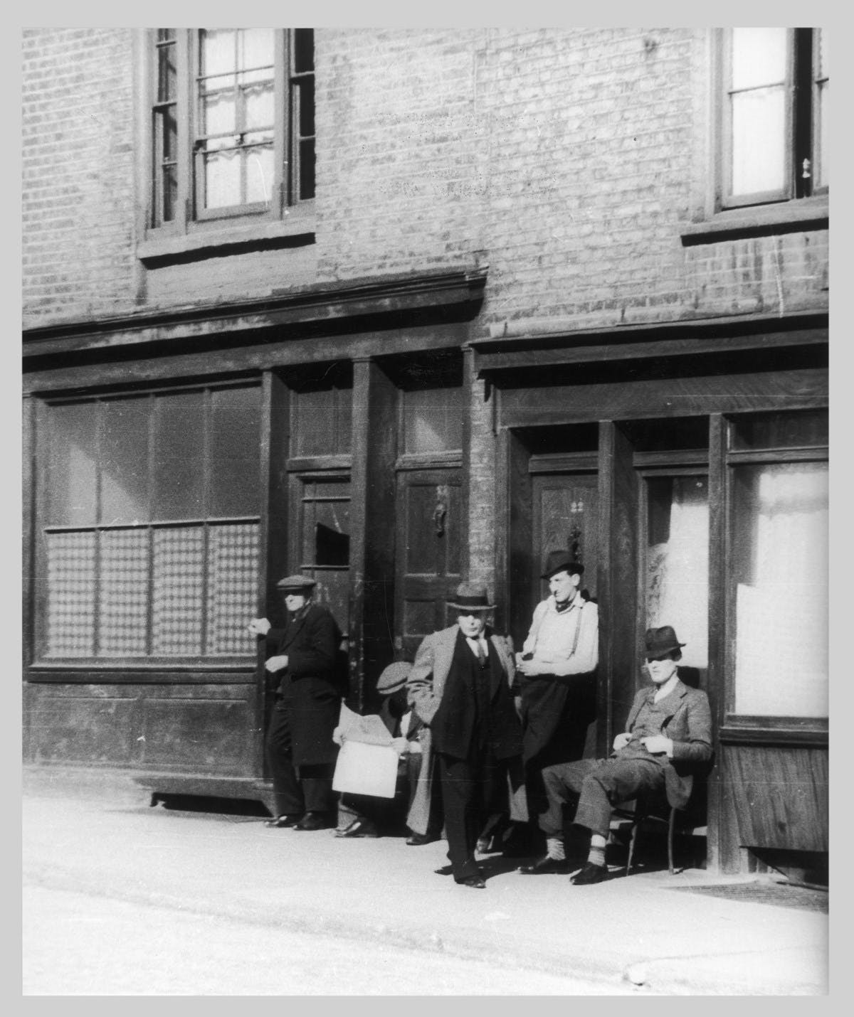 Black and white photo of a group of five unemployed Italian men, in front of an empty storefront (maybe from a restaurant or bar). They all wear hats. Three of them are standing, and two are seating with one of the sitting men reading the newspaper.