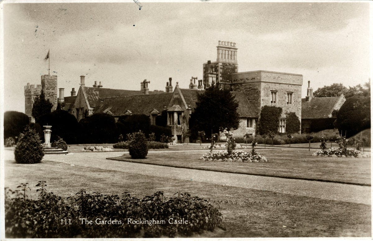 A sepia-toned postcard showing Rockingham Castle in the distance beneath a cloudy sky. In the foreground are long, low gardens - mostly grass, with wide pathways and some small bushes.