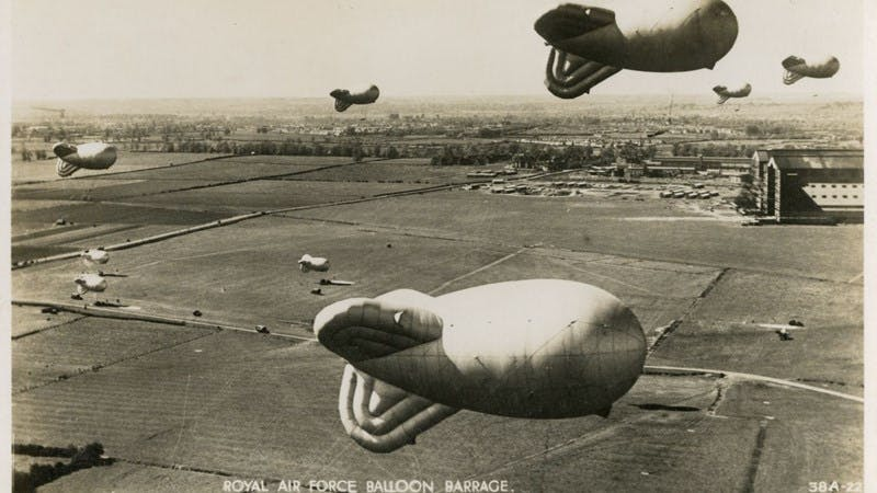 Black and white postcard of a Royal Air Force Balloon Barrage at Cardington, Bedfordshire. In the background, the airship hangars which are still there today can be seen.