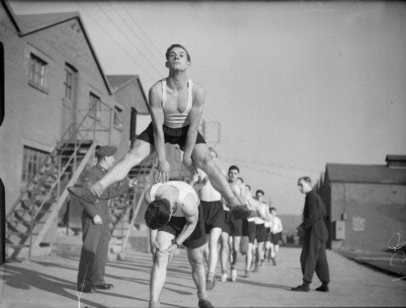 Black and white photo of soldiers from the Hampshire regiment during physical training at Oakridge farm in Bassington. The men training are performing leapfrog exercises in line. They are all wearing black shorts and white vests. A superior and another unidentified man are watching them.