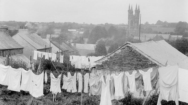 Black and white photo of the back gardens of some cottages at Buckland, near Yelverton, South Devon, England. A lot of washing is hanging on the lines.