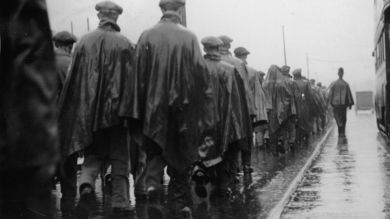 A black and white photo of a group of men walking during the Jarrow March to London in 1936, one of the most famous Hunger Marches during the Great Depression. The photo is taken from behind the group of men, meaning only their back is visible.