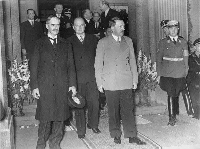 A black-and-white photograph of Neville Chamberlain and Adolf Hitler walking out of a grand entrance-way. In the background, other gentlemen in suits converse.