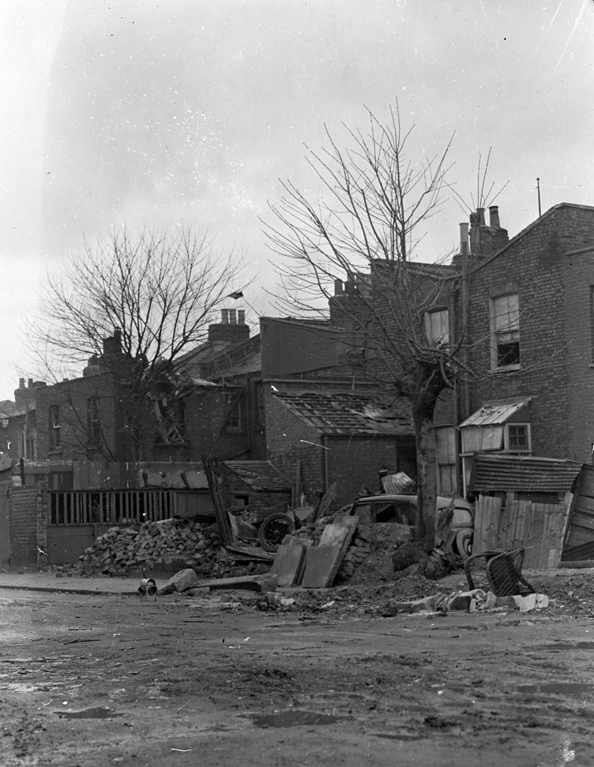 A black and white photo of houses on Peckham Hill Road. The road has suffered bomb damage from the Blitz. There is a damaged car, rubble and a chair lying on the side of the road.