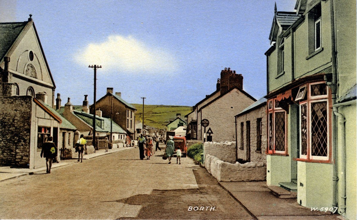 A brightly-coloured postcard showing a small high street, with green fields and blue skies in the distance.