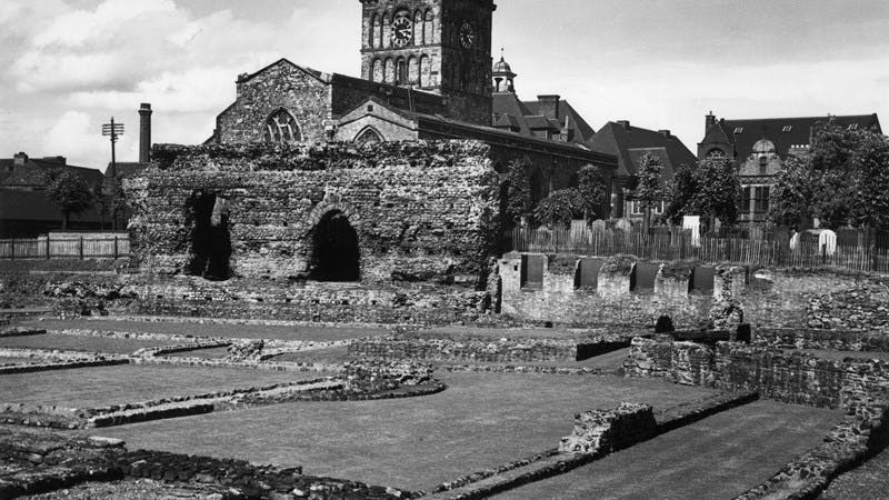 A black-and-white photo showing a large church, with low Roman ruins in the foreground.