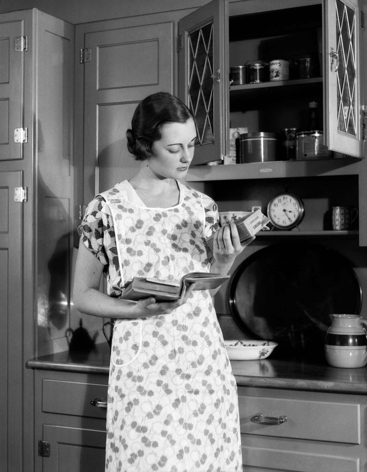 Black and white photo of a housewife wearing an apron in a kitchen. She is standing in front of a cupboard, holding a cookbook in one hand and reading a package of cornstarch from her other hand.