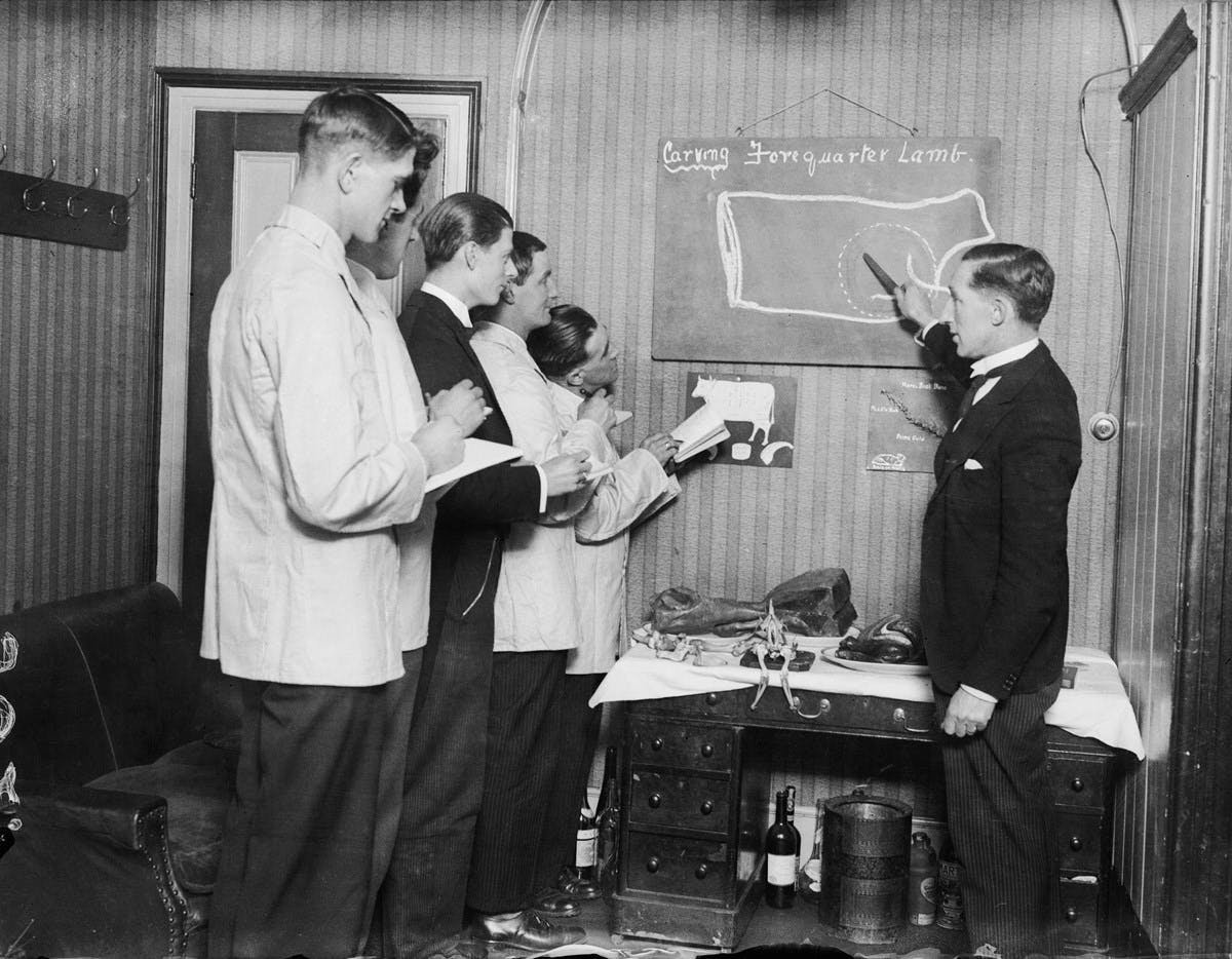 A black-and-white photograph of a butler teaching trainee butlers. The butler points to a blackboard showing the correct way to carve lamb. The trainee butlers stand attentively, with notebooks in hand.