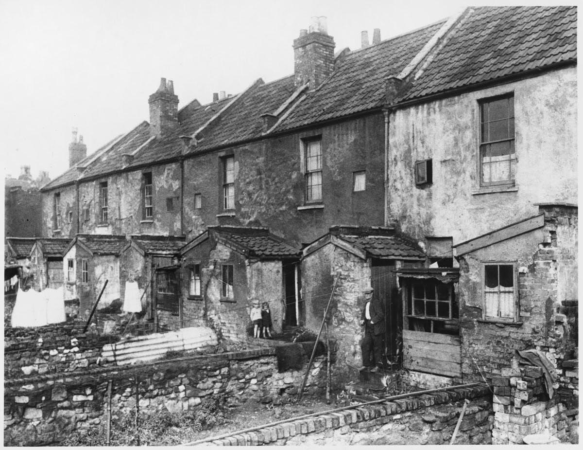 A black-and-white photograph shows the back of a row of dilapidated houses and their small gardens. Two very young children stand by one of the doors.