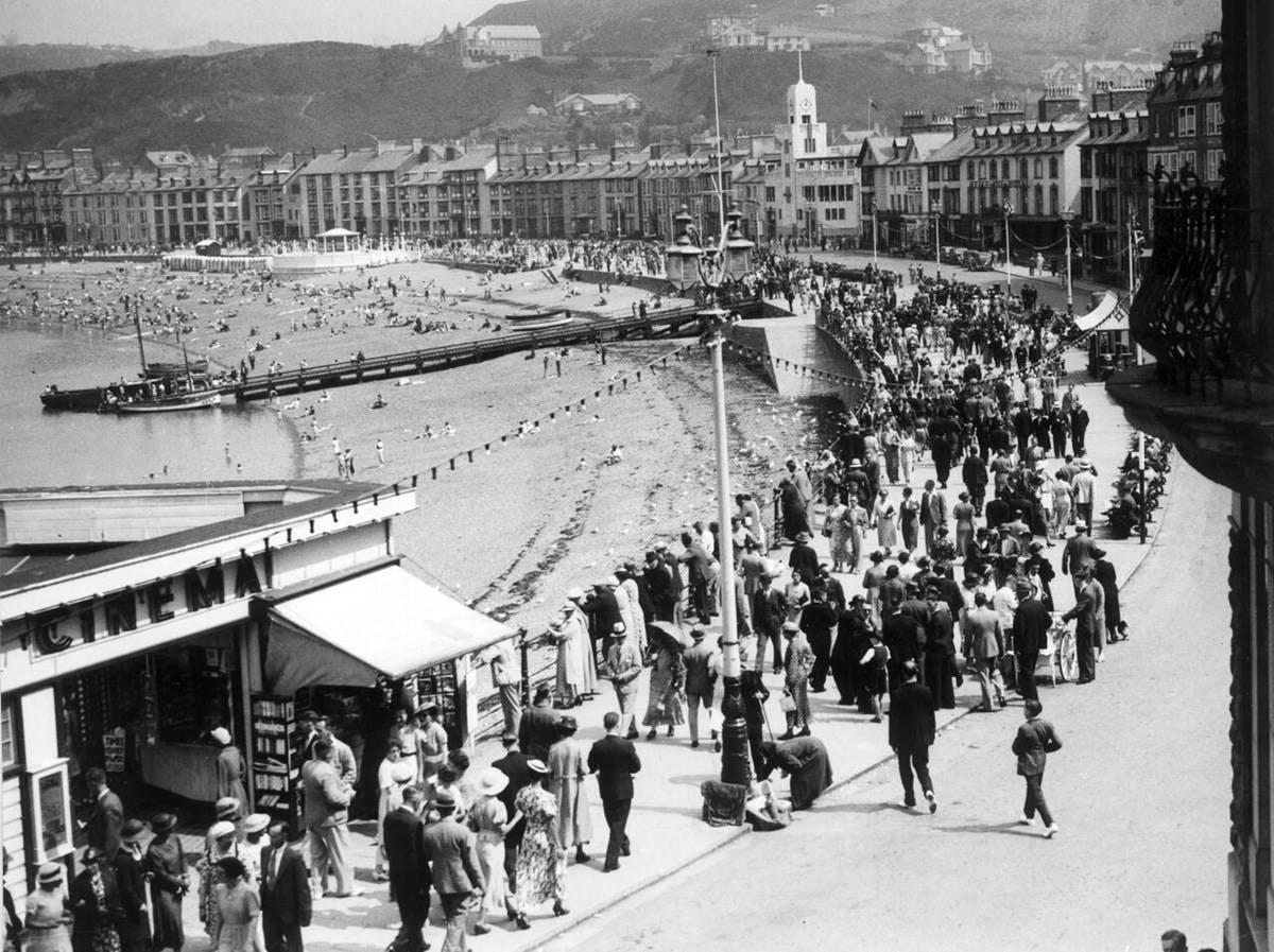A black-and-white photograph of a busy beach promenade.