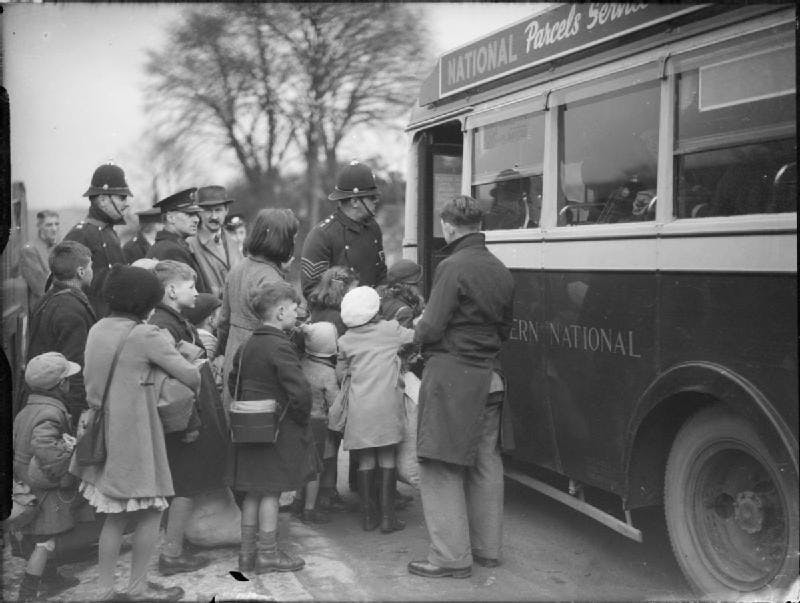 A black and white photograph of children being helped on to a bus by policemen.