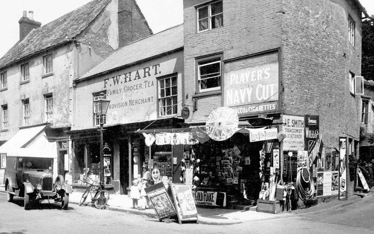 A black-and-white photograph showing a shop on a street corner. There is a car parked on the street, and a bike leaning against a street lamp. Around the shop there are many tobacco advertisements.