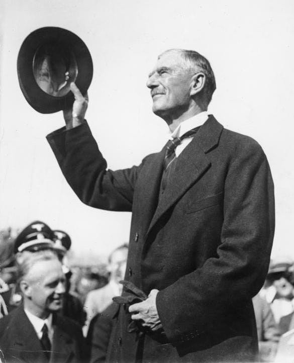 A black-and-white photograph of Neville Chamberlain standing in front of a crowd and lifting his hat to them.