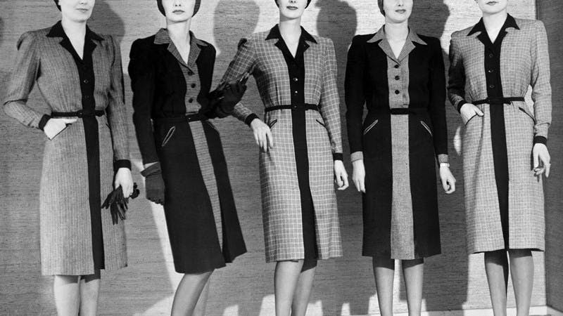 A black and white photograph of five women wearing suit dresses.
