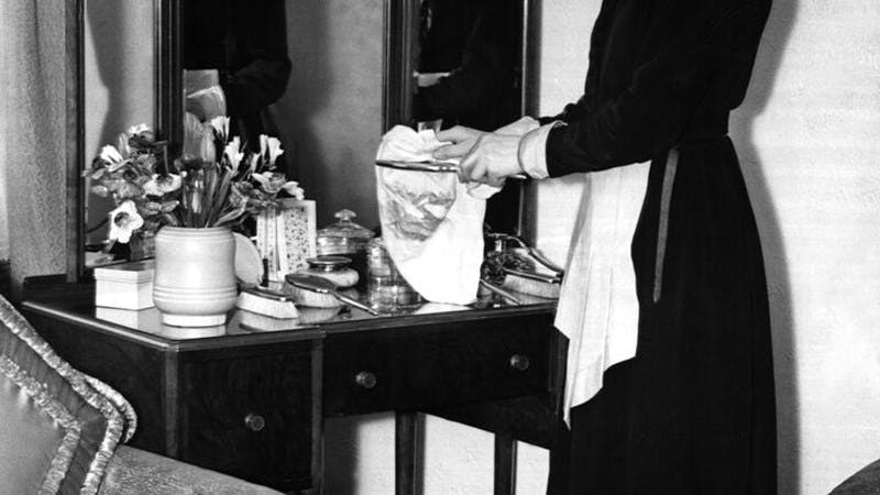 A black-and-white photograph of a maid tidying a dresser.