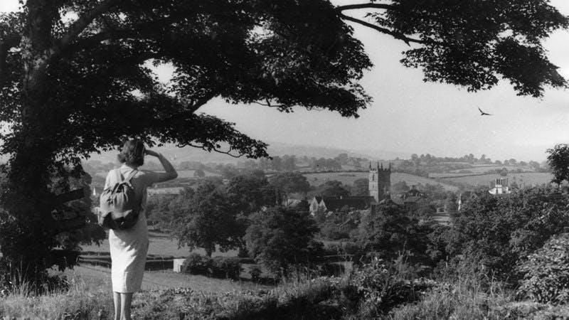 A black-and-white photograph showing a woman hiker pausing beneath a tree and looking down upon a small town in a low valley.