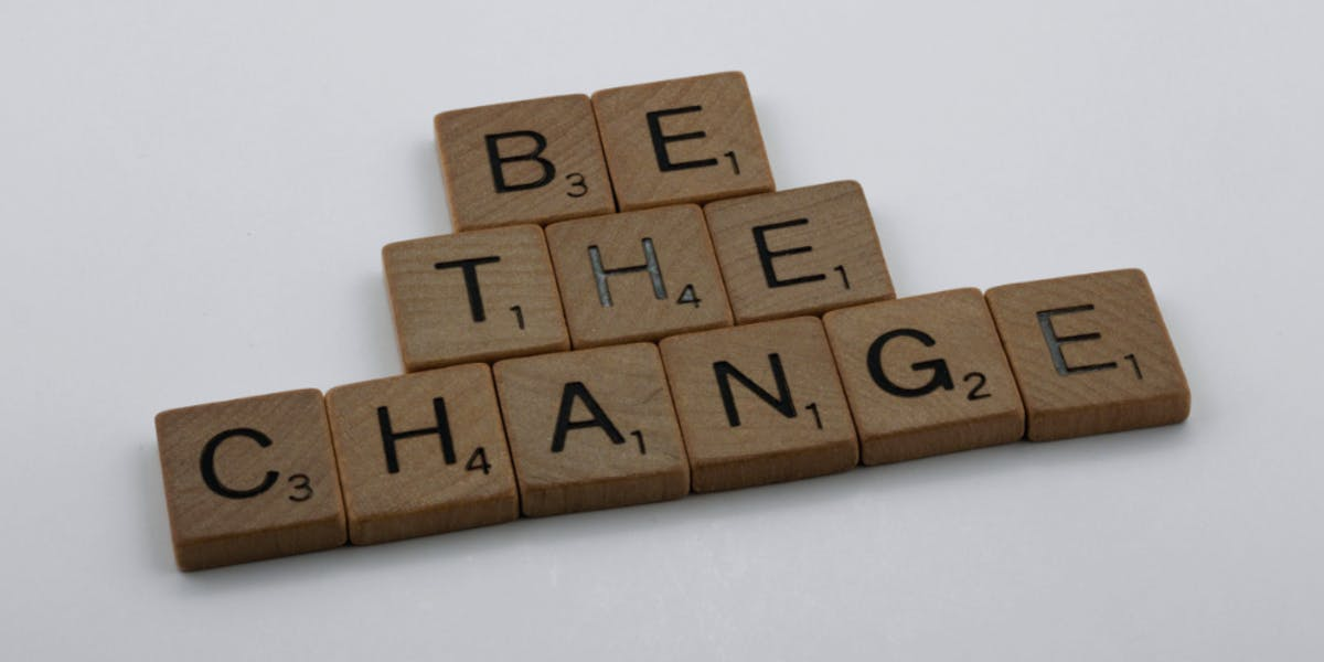 """Wooden block letters with the inscription """"Be the change""""."""