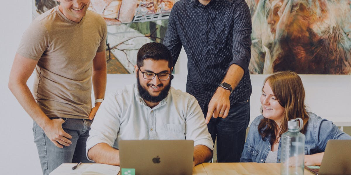 Employees smiling and sitting together while looking at a laptop.