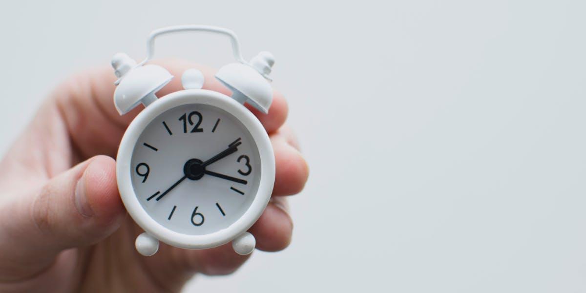 hands holding a clock