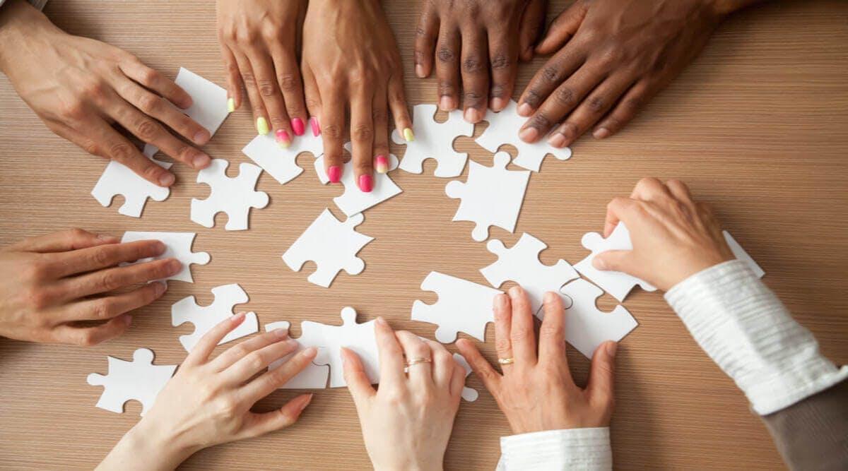 Hände die ein Puzzle zusammenlegen
