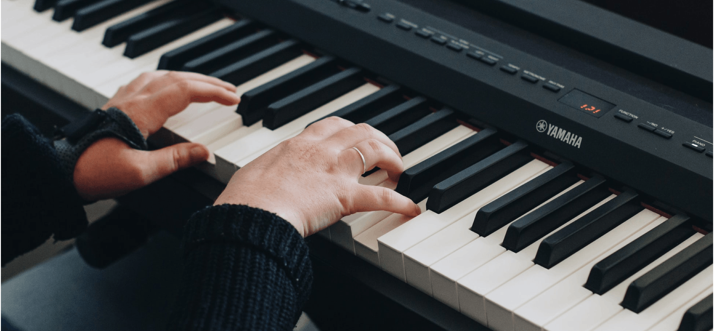 Two hands playing on a Yamaha keyboard