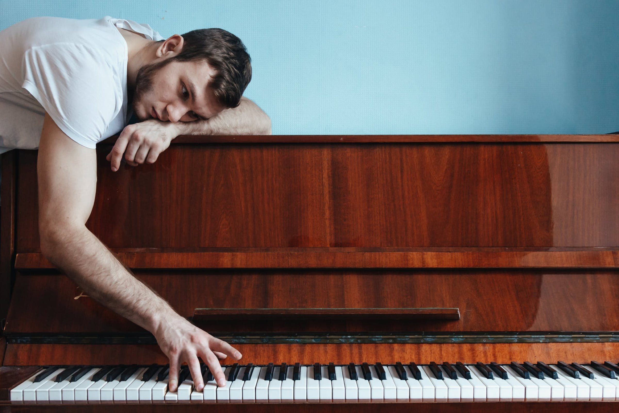 man lying on a piano