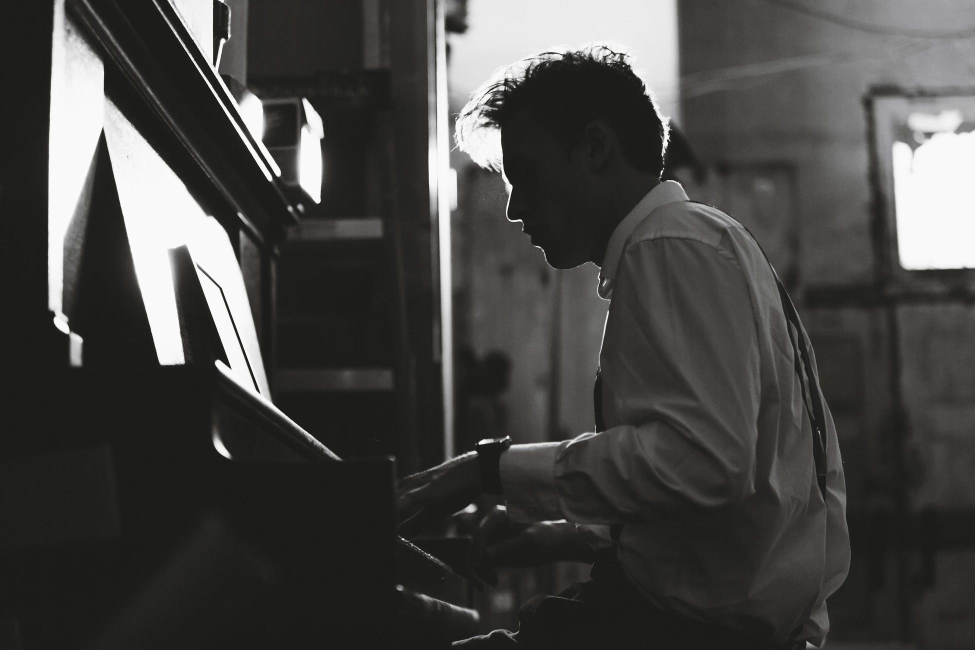 Man in white shirt is playing piano