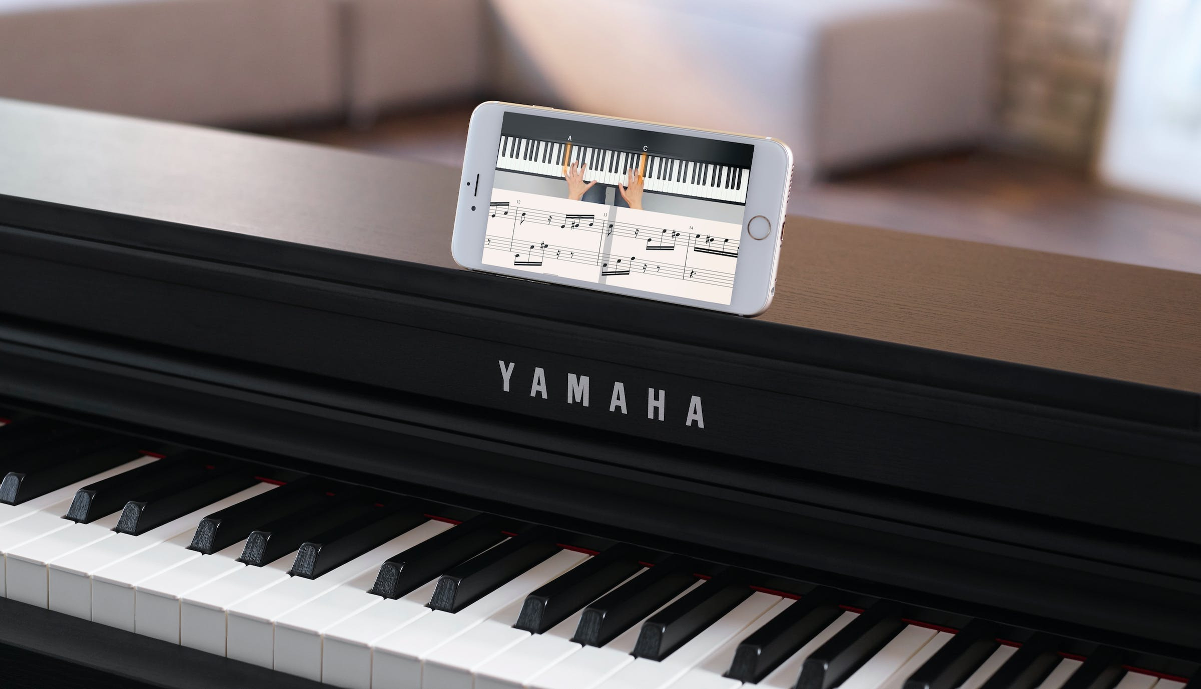 black Yamaha piano and a smartphone with flowkey