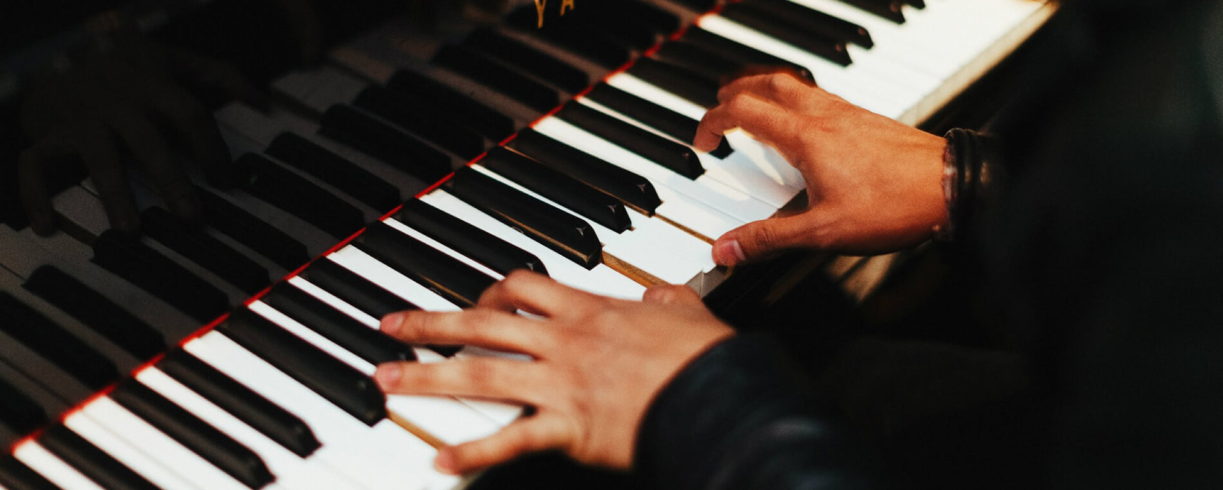 Two hands on a Yamaha piano