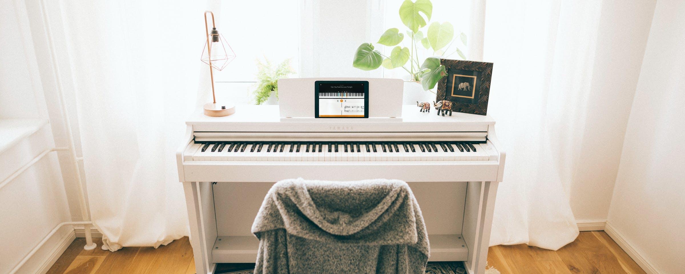 White Yamaha piano with an iPad