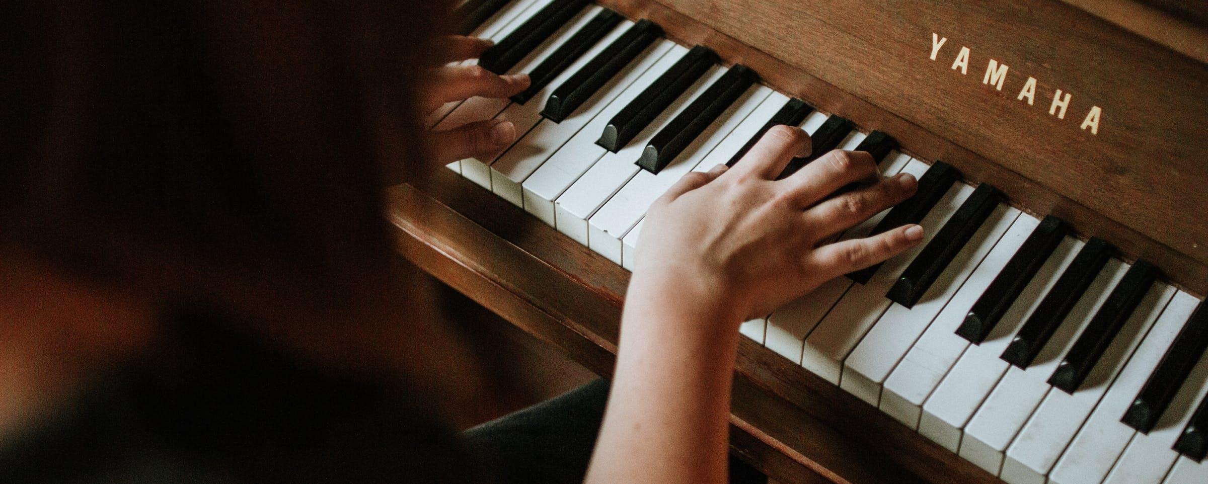 Frau spielt am braunen Yamaha Klavier
