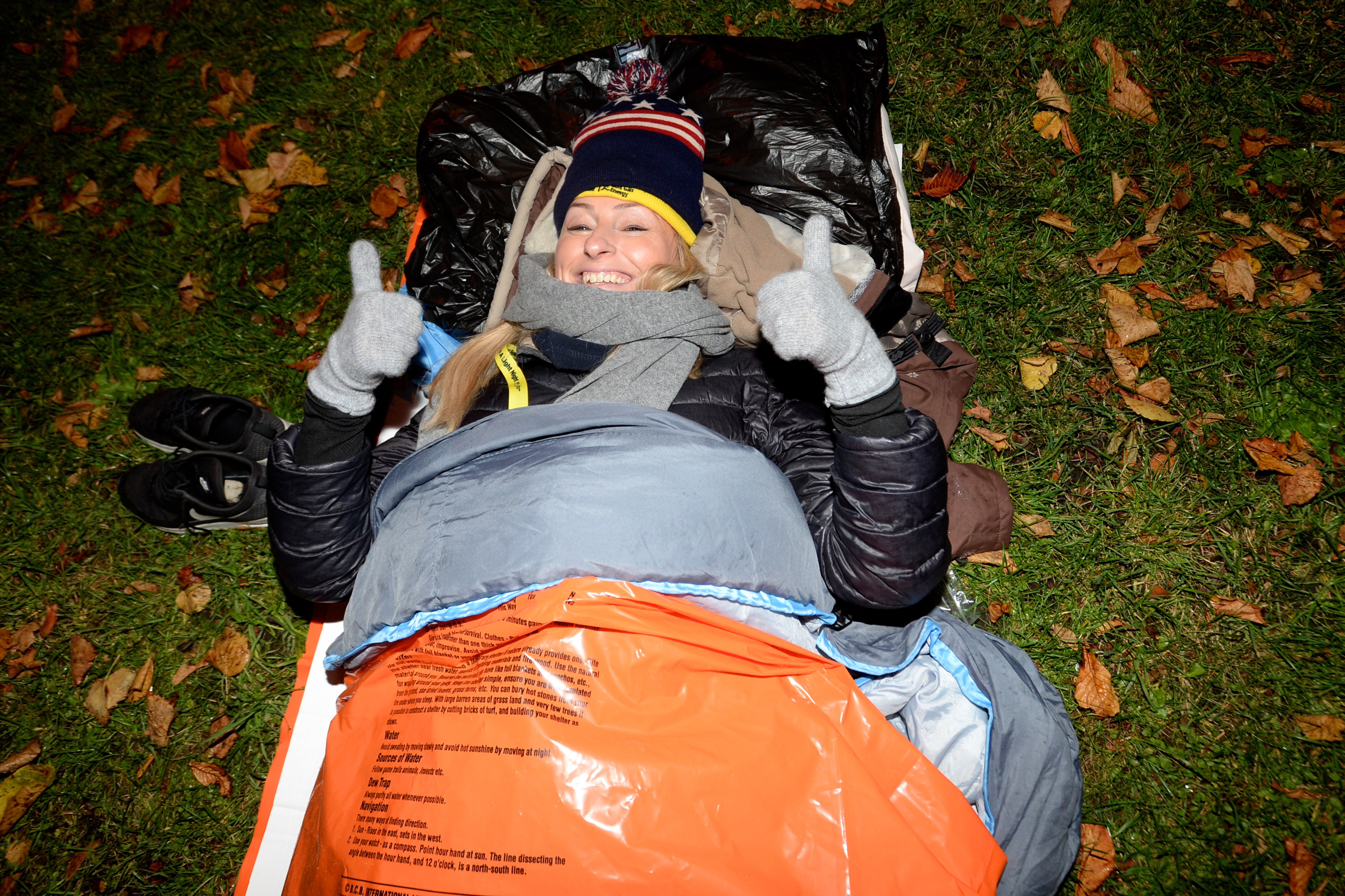 Woman in a sleeping bag outside smiling with her thumbs up to the camera