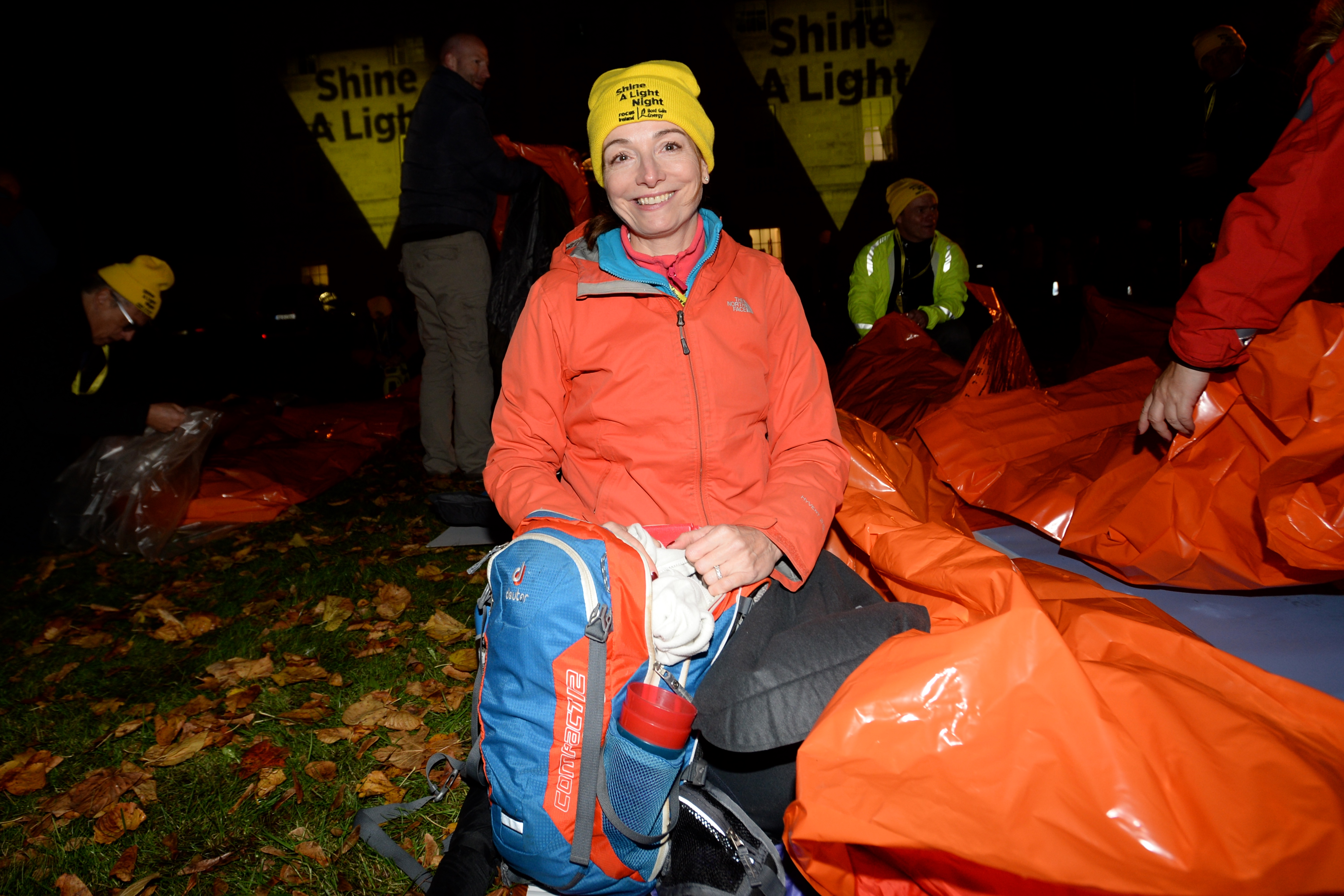Woman in her sleeping bag outside for Shine A Light Night 2020, smiling towards the camera