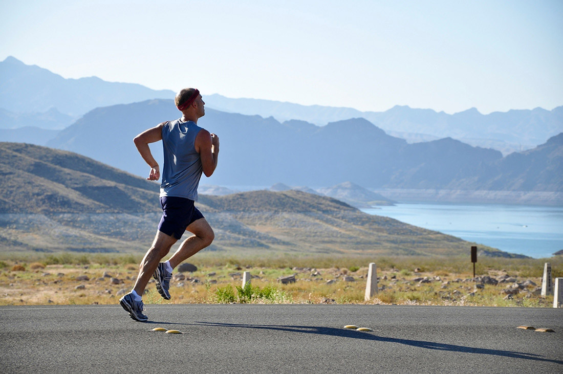 A man running along a road with hills and a blue lake in the background.