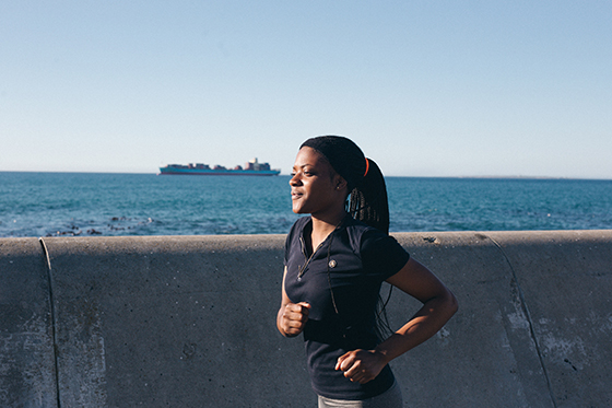 Woman in running kit running alongside the sea.