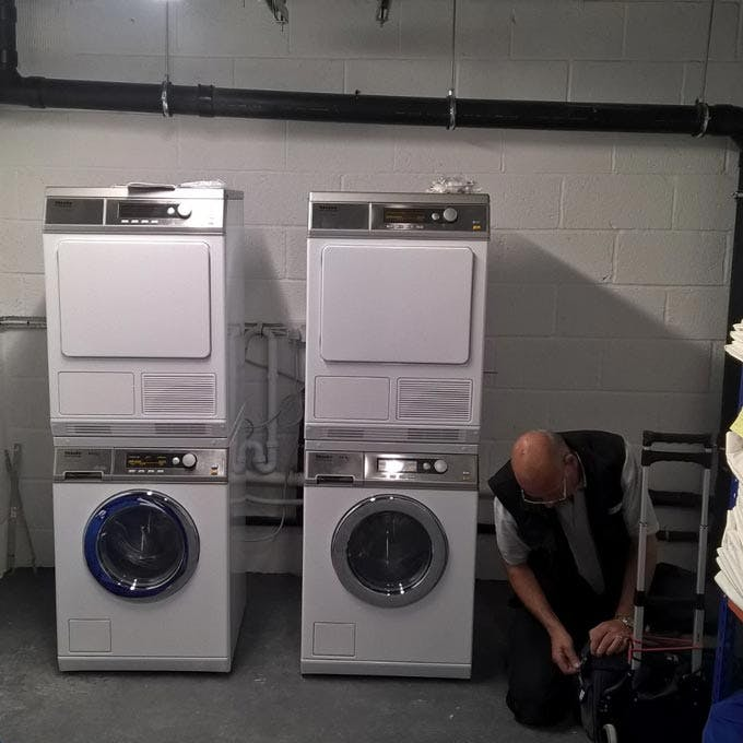 Engineer kneeling next to commercial washing machines