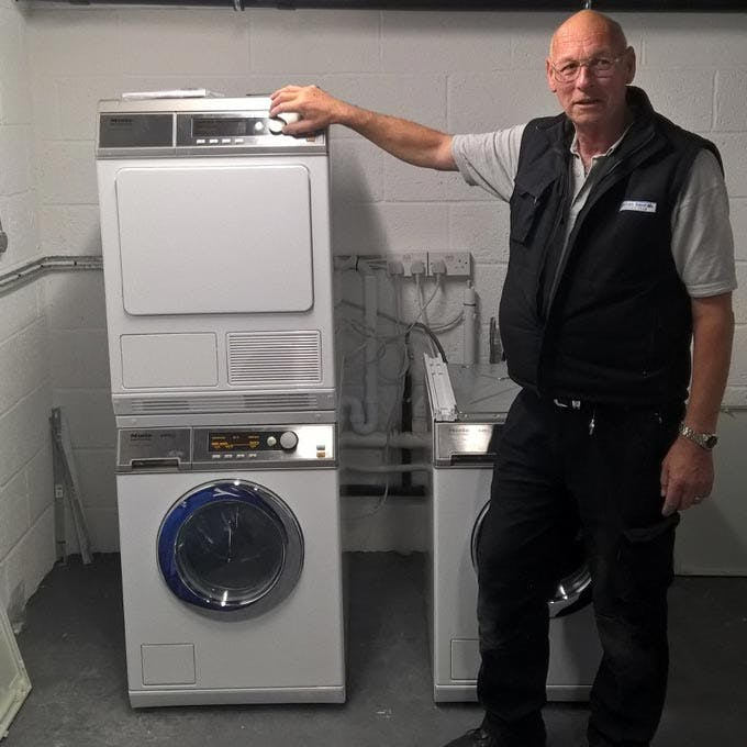 Engineer standing next to commercial washing machines