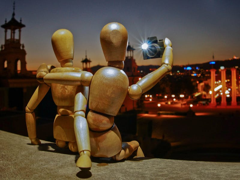 Two wooden mannequins taking a selfie in front of a cityscape.