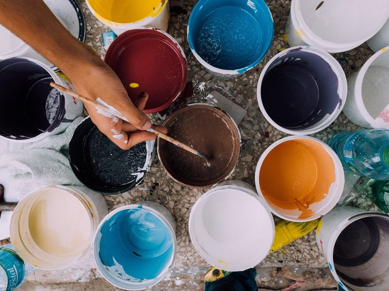 A collection of opened tins filled with different colours of paint, with an artist dipping their brush in.