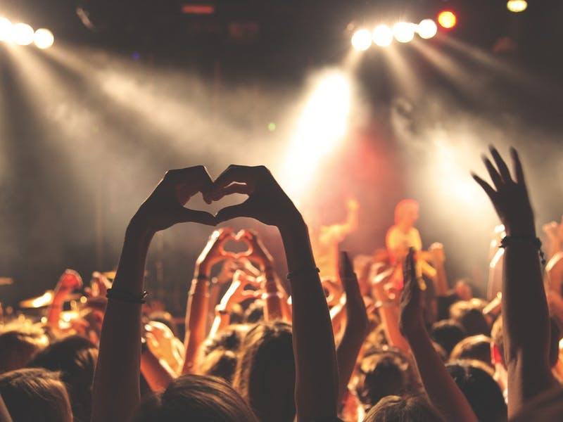 A person making a heart sign with their hands at a live music event.
