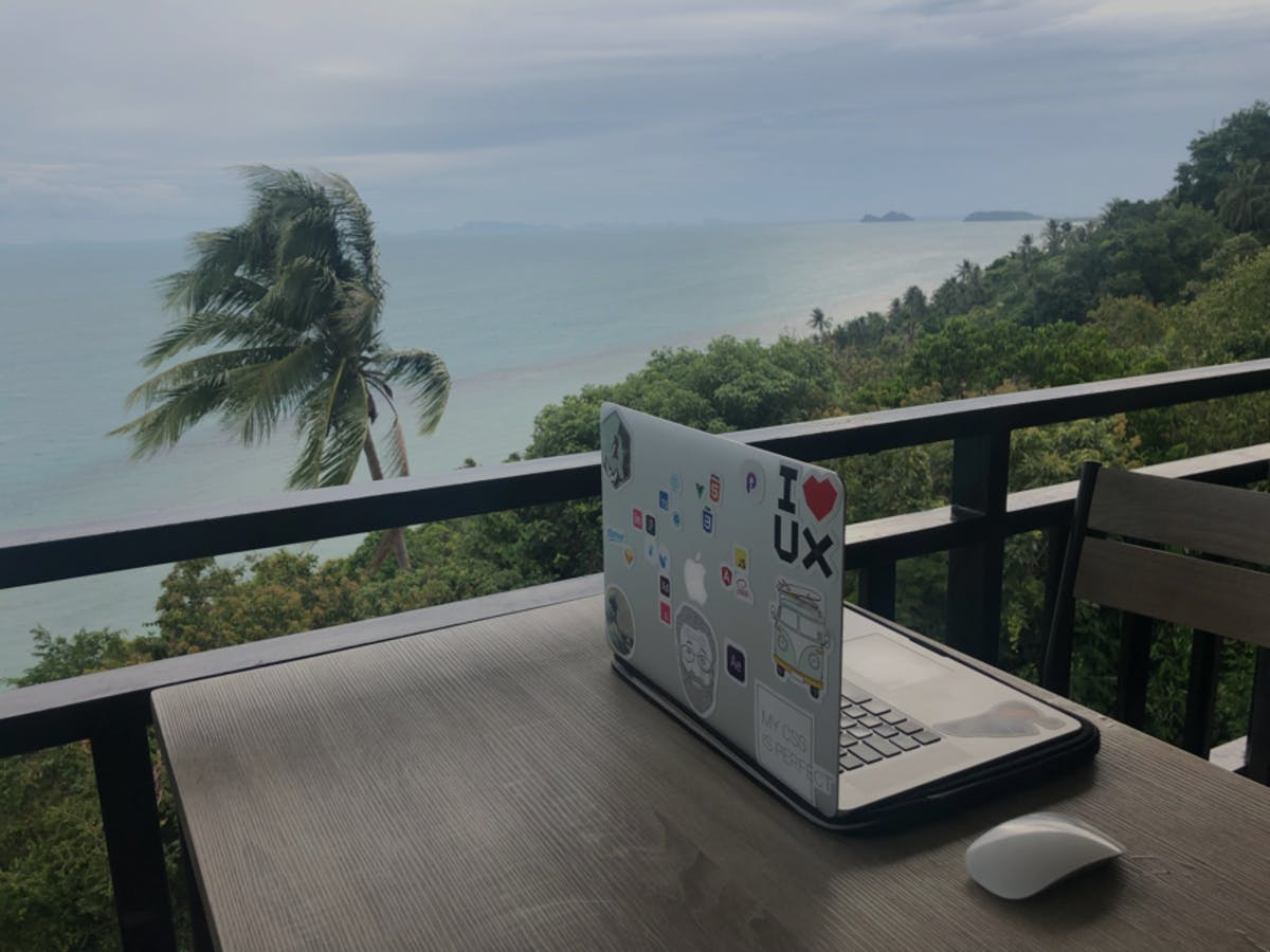 Picture of laptop in hill-top restaurant with views of the sea, mountains and palm trees