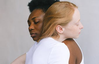 A close-up of a Black woman and a white woman hugging.