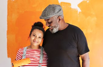 Senior man with daughter standing in front of a wall that they're painting orange.