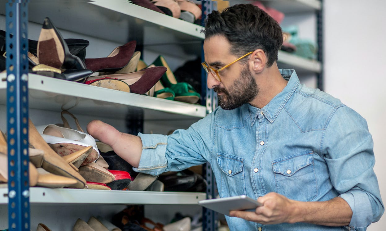 Man with a physical disability is using a digital tablet while examining shoes on shelf.