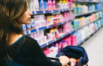 A young mother with a stroller is shopping in a store aisle with multicolor product packaging.
