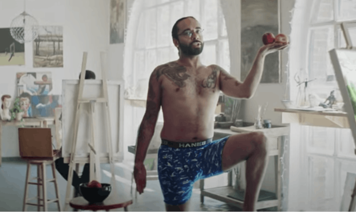 A man wearing underwear and holding apples shows body self-confidence while posing for artists.